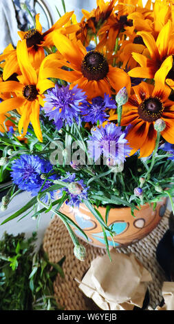 Closeup on a summer bouquet of rutbeckia and cornflowers in an earthenware jug with authentic painting, selective focus - Stock Photo