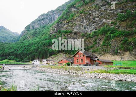 School in Village Flam in Norway. Flam village in Flamsdalen, inner end of Aurlandsfjorden, branch Sognefjorden. Wooden school near the river in the - Stock Photo