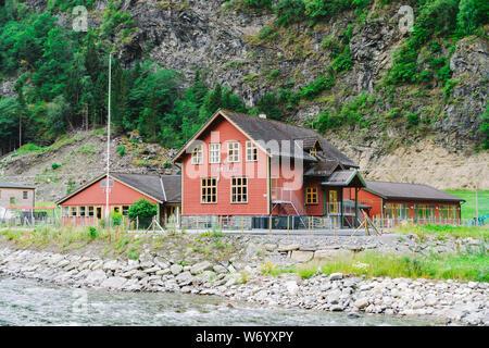 School in Village Flam in Norway. Flam village in Flamsdalen, inner end of Aurlandsfjorden, branch Sognefjorden. Wooden school near river in mountains - Stock Photo