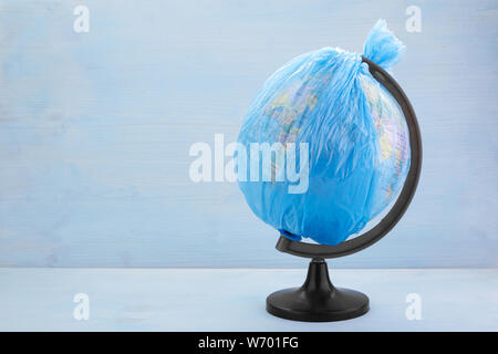 Globe of planet Earth dressed in a garbage plastic bag on blue wooden background - Stock Photo