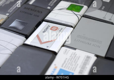 KHARKIV, UKRAINE - JULY 30, 2019: Bunch of old used mobile phone batteries. Recycling electronics was sold in the market cheap. Close up top view - Stock Photo