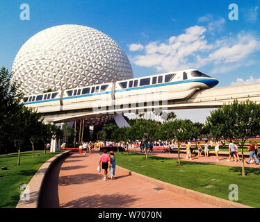 A Walt Disney World monorail train glides above visitors heading to a huge geodesic sphere called Spaceship Earth that is the symbol of Epcot, one of four theme parks within the world-famous Disney amusement complex near Orlando in Florida, USA. Epcot is an acronym for Experimental Prototype Community of Tomorrow and was originally planned to be a utopian city. However, it has evolved  into two themed areas: Future World, showcasing science and technology, and World Showcase, featuring the lifestyles of 11 different countries. Since opening in 1971, Disney World has become an American icon. - Stock Photo