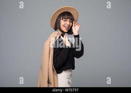 Young beautiful fashionable woman wearing stylish eyeglasses, fake fur coat, hat. Female fashion, beauty concept. Outdoor. Close up. - Stock Photo