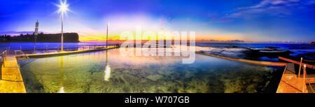 Mona Vale beach rock pool at sunrise in wide panoramic view under bright electric poles facing rising sun over Pacific ocean horizon - Sydney Northern - Stock Photo