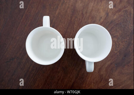 two little coffee cups, blue and red over a brown wooden table with a withe background - Stock Photo