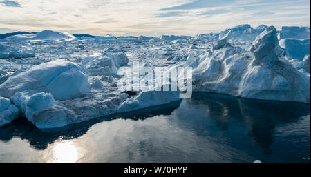 Aerial drone image of Iceberg and ice from glacier in arctic nature landscape on Greenland. Aerial image drone photo of icebergs in Ilulissat icefjord. Affected by climate change and global warming.
