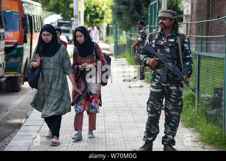 Kashmiri residents walk next to Indian Troops standing on guard as Additional Indian Troops arrive in Srinagar.Fear and confusion have gripped residents in India administered Kashmir after authorities on Thursday issued unprecedented order, cancelling a Hindu pilgrimage and asking tourists to leave the disputed region and 25000 additional Indian forces arrived to the disputed region. The order led to panic in Kashmir which has remained tense for the past few days after the Centre ordered deployment of 100 companies of additional troops in the Valley. - Stock Photo