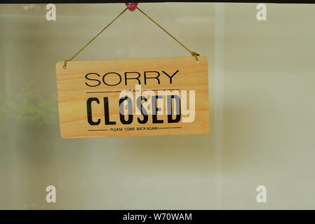 Closeup of generic wooden closed sign read sorry we are closed, please come back again, hanging on glass window of a shop - Stock Photo