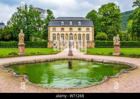 The abbey garden in Echternach - the oldest town in Luxembourg, with a fountain and the building of the Orangery on an overcast May day - Stock Photo