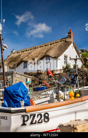 UK, England, Cornwall, Sennen Cove, fishing boats on slipway before thatched seafront holiday cottage - Stock Photo