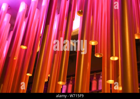 Abstract installation of plastic tubes in the interior. Unusual chandelier. - Stock Photo