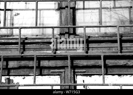 Old window painted white paint behind a rusty bars closeup, black and white - Stock Photo
