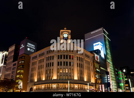 Night view of art deco Wako Building with its iconic Clocktower symbol of the Ginza fashion and boutique district in the very center of Tokyo - Stock Photo