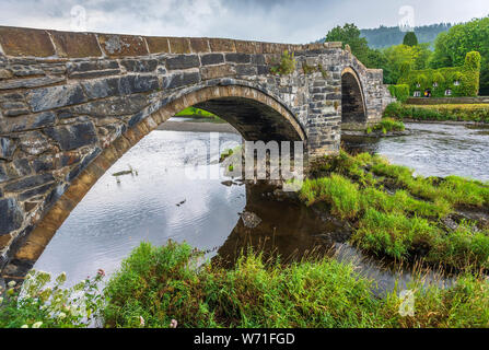 Stone roadbridge over the river Conwy at Llanrwst with the Virgina creeper covered tearoom in the background. - Stock Photo