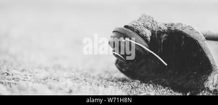 String trimmer on mown grass, close up. Theme of lawn care services, tool rental or repair. Banner format background with copyspace. Monochrome, matte - Stock Photo