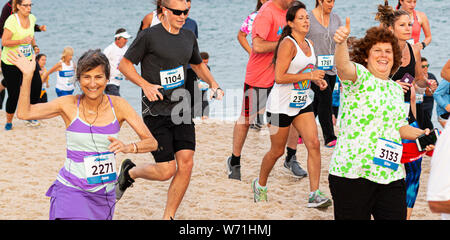 Babylon, New York, USA – 24 June 2019: Two women wave and give thumbs up while running a crowded one mile race on the beach by the water at the Robert - Stock Photo