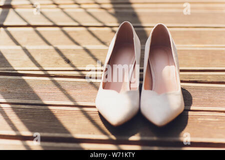 Close Up Still Life of Pair of Plain White Bridal Shoes with High Heels Resting on Rustic Wooden Floor or Table with Copy Space in Selective Focus. - Stock Photo