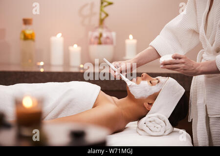 Side view portrait of beautiful mixed race woman enjoying facial therapy in spa, copy space - Stock Photo