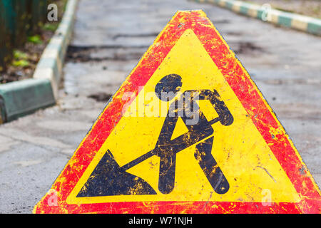 A sign of a man with a shovel. Caution, road works are under way - Stock Photo