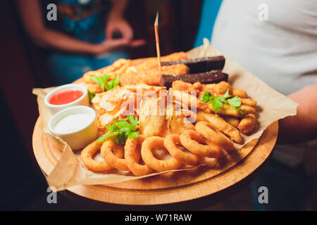 Assorted beer snacks: onion rings, cheese balls, chips etc on a iron tray on a dark wooden background among vegetables. Close-up. Space. - Stock Photo