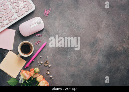 Flat lay women workspace - modern keyboard, mouse, cup of coffee, rose flowers, jewelry and stationery on a dark rustic background. Feminine office ta - Stock Photo