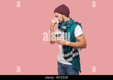 Portrait of sickness modern bearded young hipster man in white shirt and casual hat standing,sneezes of napkin, holding hot drink in paper cup. Indoor - Stock Photo