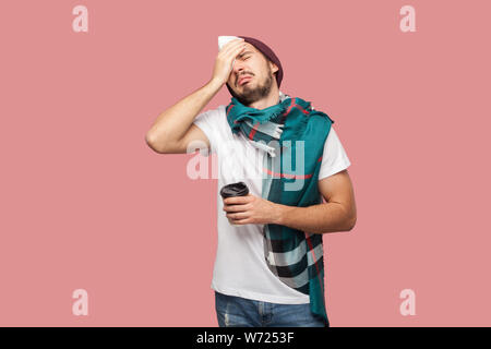 Sickness modern bearded young hipster man in white shirt, hat and scarf standing, touching with hand his head, have strong headache, holding hot tea i - Stock Photo