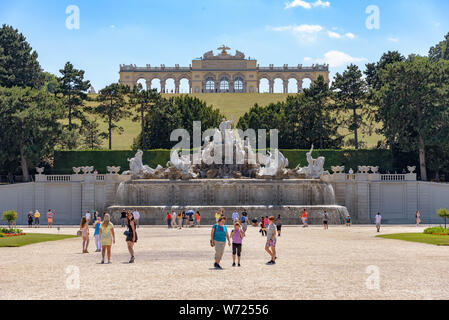 The Neptune Fountain with the Gloriette behind it in Schonnbrunn Gardens on a sunny summer day - Stock Photo