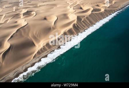 Aerial view of Skeleton coast sand dunes meeting the waves of Atlanic ocean. Skeleton coast, Namibia. - Stock Photo