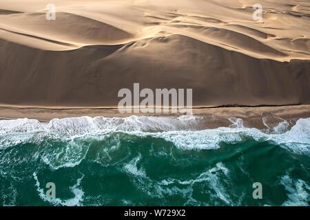 Aerial view of Skeleton coast sand dunes meeting the waves of Atlanic ocean. Skeleton coast, Namibia. - Stock Photo
