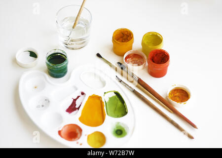 Gouache multi-colored paints, brushes, palette and a glass of water for brushes on a white background