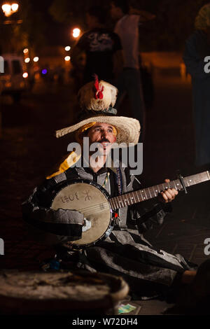 Morocco, Marrakesh. A man with a rooster on his head plays banjo and sings in Djemaa el Fna Square at night - Stock Photo