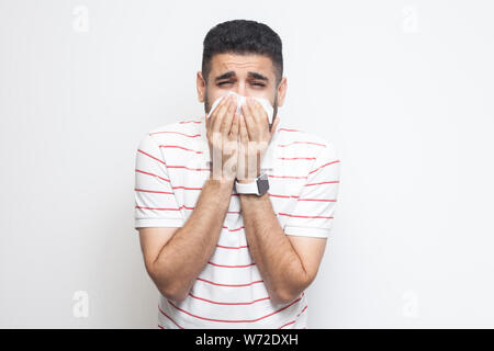 Cold and flu. Portrait of sick bearded young man in striped t-shirt standing, holding tissue on mouth and looking at camera with sadness and illness. - Stock Photo