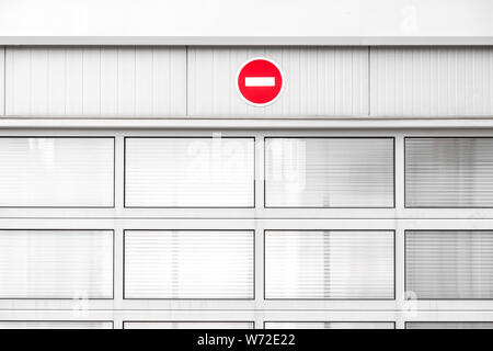No entry traffic sign on gray industrial wall, minimalist architecture with warning road sign, red color pop up - Stock Photo