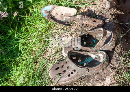 Garden clogs and shovel standing on the mud. - Stock Photo