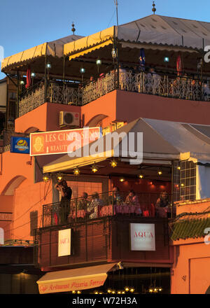 A view of the high terraces of restaurants overlooking Jemaa El Fna Square. - Stock Photo