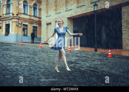 Beautiful blonde woman runs barefoot on the road in the rain. - Stock Photo