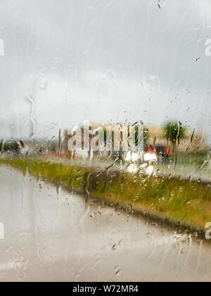 Rainy day rain drops raindrops through car side window blurred background traffic passing by cars vehicles on road - Stock Photo