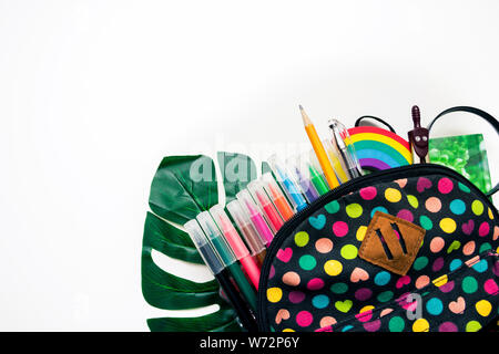 Bright colored backpack and colorful stationary school supplies on white background, space or text flat layer. Concept back to school. Close-up, copy - Stock Photo