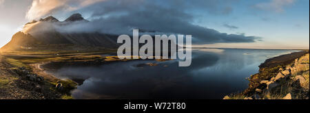 Panoramic view of a Sunset in Stokksnes, Iceland with Vestrahorn mountain obscured by clouds, and water in the foreground. - Stock Photo