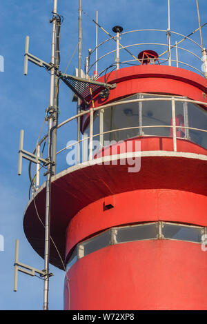 Top of the lighthouse close-up on a background of blue sky. Visible antennas, windows with glass where the lamp is installed. - Stock Photo