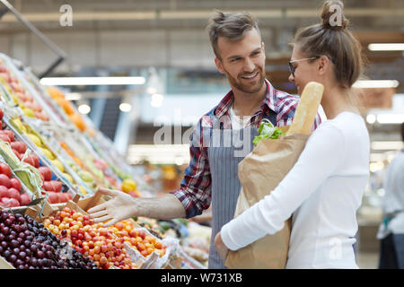 Waist up portrait of handsome young man helping customer choose fruits in supermarket, copy space - Stock Photo