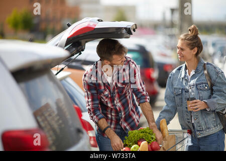 Portrait of young couple packing groceries into car trunk outdoors, copy space - Stock Photo