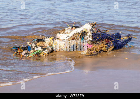 Fishing nets and pollution rubbish washed up from the Atlantic Ocean onto a sand beach in Agadir, Morocco - Stock Photo