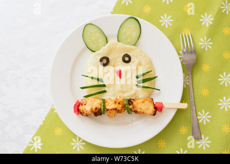 Baby puree in the form of a hare and rabbit. Mashed potatoes. Children's menu on a green background - Stock Photo