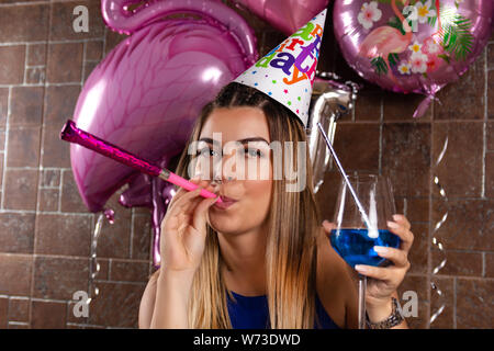Girl with musical blowouts and cocktail blue lagoon in hand and cap on the head celebrates her birthday in a night club. Birthday party concept - Stock Photo