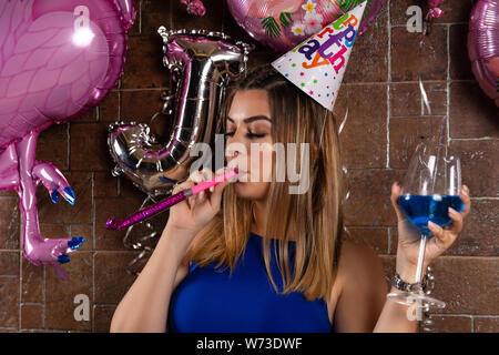 Happy beautiful girl with musical blowouts and cocktail blue lagoon in hand and cap on the head celebrates her birthday in a night club - Stock Photo