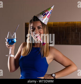 Happy girl with musical blowouts and cocktail blue lagoon in hand and cap on the head celebrates her birthday in a night club. Birthday party concept - Stock Photo