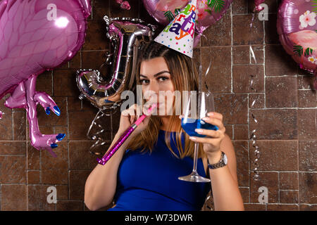 Happy young girl with musical blowouts and cocktail blue lagoon in hand and cap on the head celebrates her birthday in a night club. Birthday party - Stock Photo