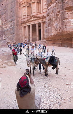 A group of tourists & 2 donkeys pose for a photo in front of the Treasury, an elaborate temple in the ancient city of Petra in Jordan. - Stock Photo